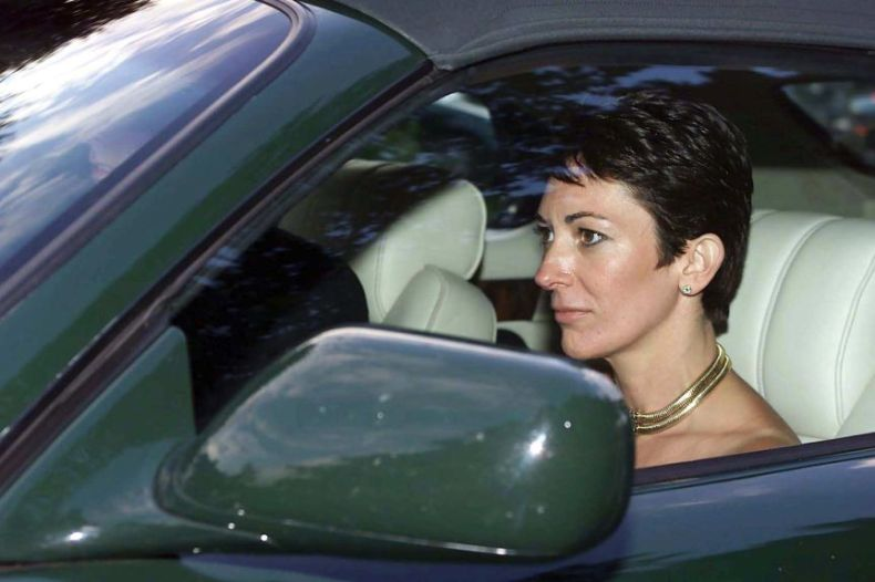 A woman with short hair drives a soft-topped sportscar , while wearing a large gold necklace.