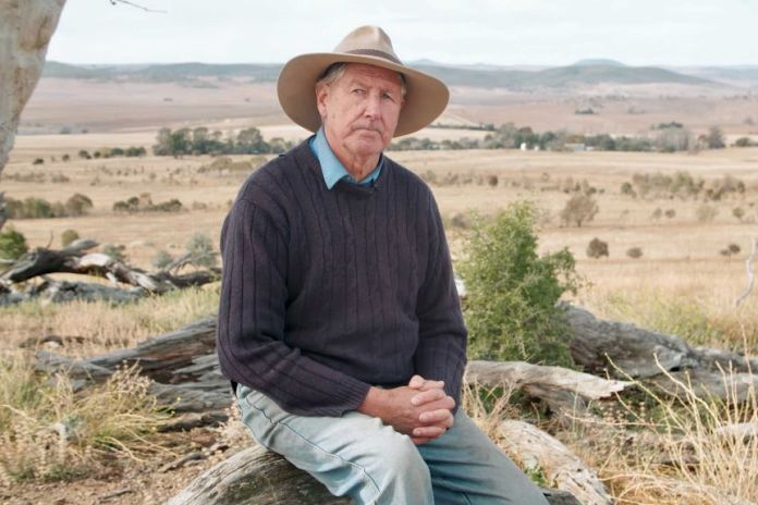 A farmer wearing a wide-brim hat and a wearing a sweater sits on his dry property