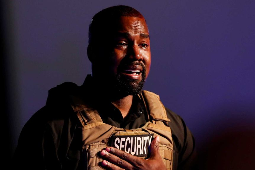 """Kanye West holds his hand to his heart with tears in his eyes, wearing a military vest with the word """"security"""" on it"""