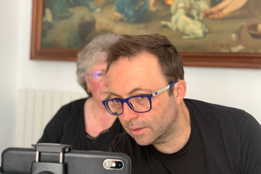 Director Luke Eve looking at an iphone on a tripod, his mother Karen sitting in the background