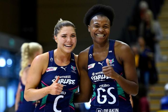 Two Melbourne Vixens super netball players smile as they celebrate as they beat the Giants.