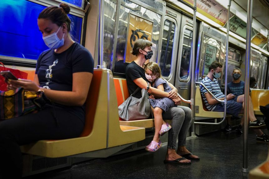 A child rests on a subway car while riders wear protective masks.