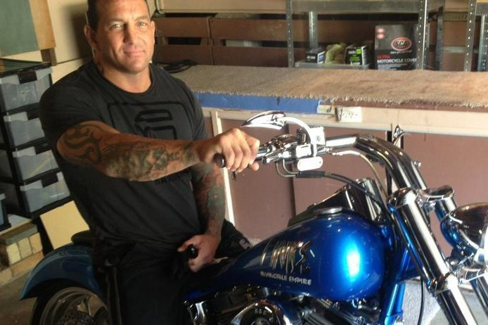 A middle-aged man with tattoos on his arms and black T-shirt and trousers sits on a blue motorcycle.