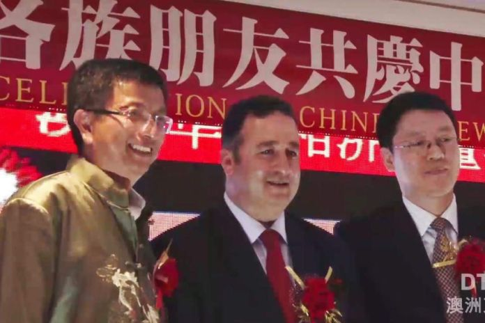One man in a gold jacket and two men wearing suits and ties standing on stage in front of red banner