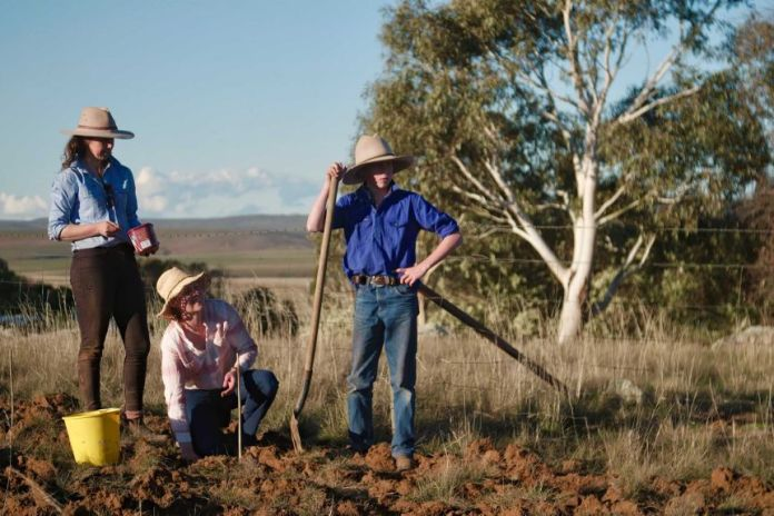 A teenage boy and two woman stand by a barbed wire fence on a rural property