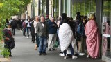 People queue outside a Centrelink in Melbourne on March 23