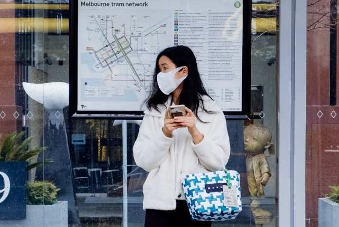 A woman wearing a face mask waits at a Melbourne tram stop.