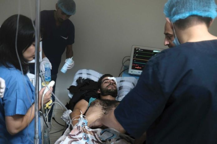 A man with dark hair and a short beard stares at the camera while lying on the bed in the hospital