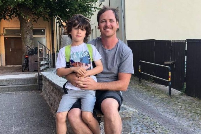 Clint Grundy and his son sit on his lap in Sweden.