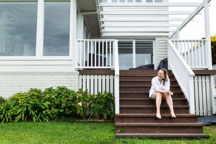 A young woman is sitting on the stairs to the porch of a white weather board house.