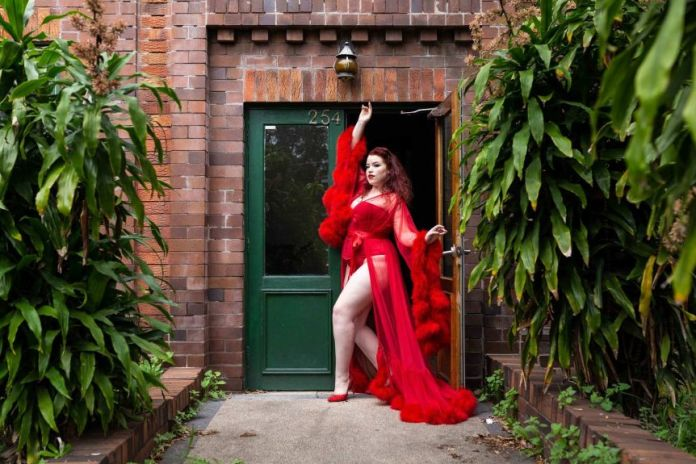 A woman makes a pose in a doorway. She wears a red corset and panties covered with a red translucent dress with furry cuffs.
