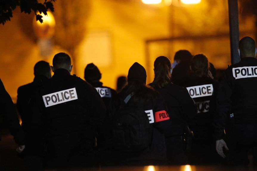 French police officers gather together in the street in the evening.