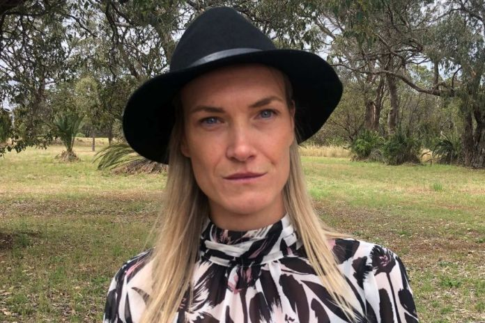 A head and shoulders shot of a woman with blonde hair and a black hat standing in front of bushland.