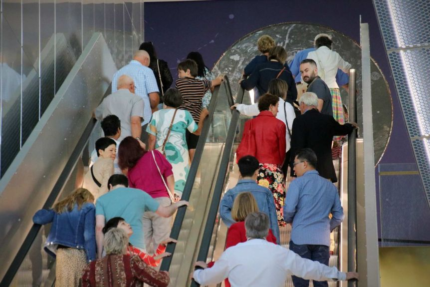 A group of people ride escalators in WA's new museum