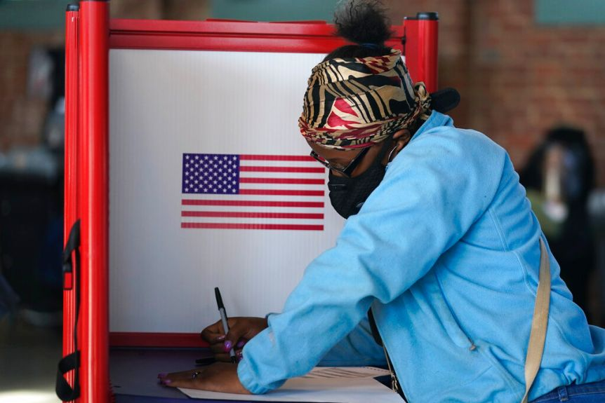 You view a woman of African American descent marking a ballot in a voting booth with a large American flag.