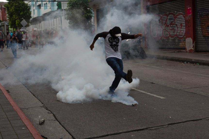 A demonstrator returns a tear gas canister fired by police near the Guatemalan Congress building