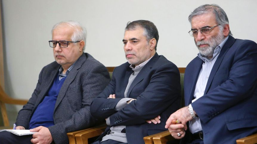You view three greying Iranian men in navy suits sitting and taking notes on wood chairs upholstered with green cushions.