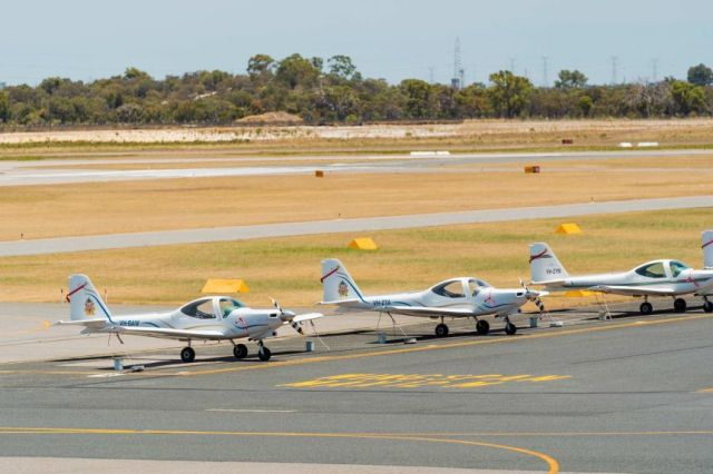 A row of small aircraft parked on the tarmac of Jandakot Airport in Perth.