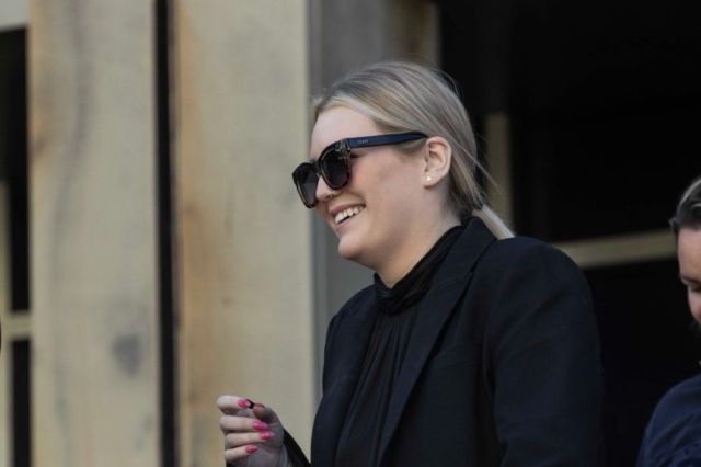 A young woman with blonde hair and glasses smiles as she walks away from the camera