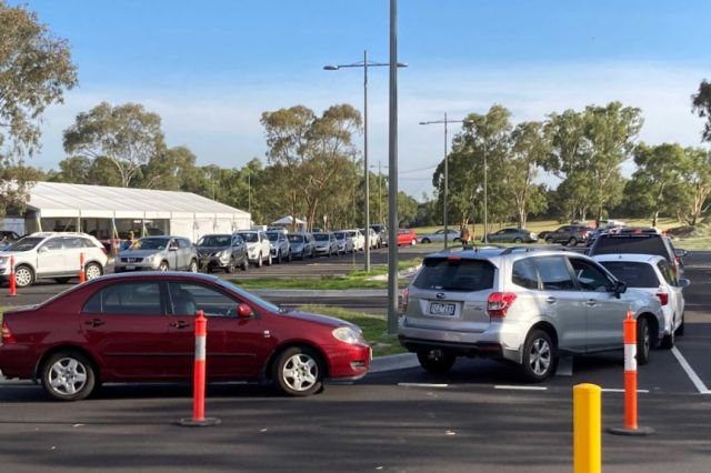 A long line of cars at a drive-through coronavirus testing site on a sunny Melbourne day.