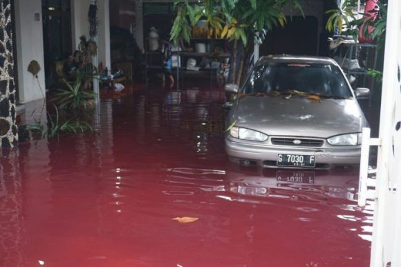 A house and carport inundated by the blood-red flood waters