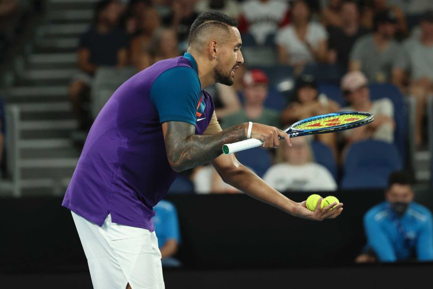 Nick Kyrgios holds his racquet horizontally above two tennis balls in his other hand, leaning slightly forward