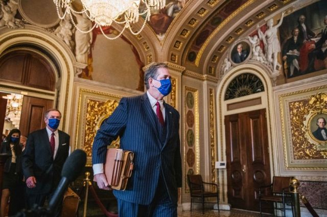 Castor wears a suit and mask and holds folders and a satchel as he walks through a grand hall past reporters