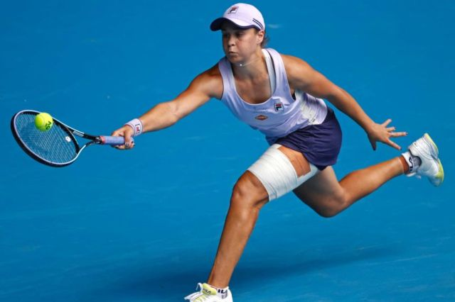 Ash Barty stretches for a forehand while wearing a bandage at the Australian Open.