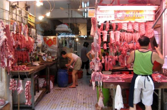 Meat hangs from hooks as two men set up their stalls in a market.