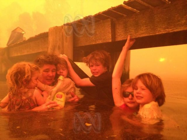 Families shelter in water next to a jetty as the bushfire sweeps through Dunalley.