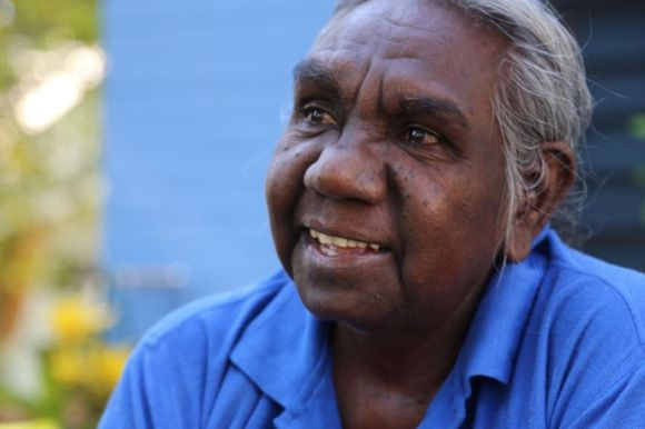 An elderly Indigenous woman speaks into a microphone.