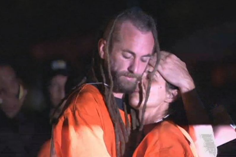 Murder accused Sara Connor and David Taylor embrace during a crime reconstruction, surrounded by Bali police officials and media
