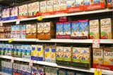 Supermarket shelf of rice, soy and almond boxes.