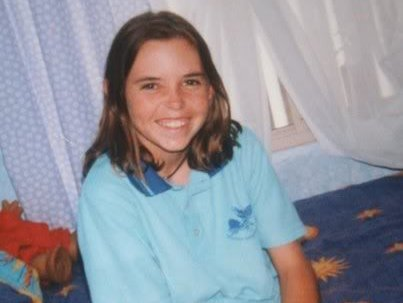 A smiling Hayley Dodd sits on a bed wearing a light blue school polo shirt.
