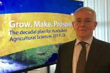 Dr Jeremy Burdon stands in front of signage reading: 'Grow. Make. Prosper: decadal plan for Australian agricultural sciences'