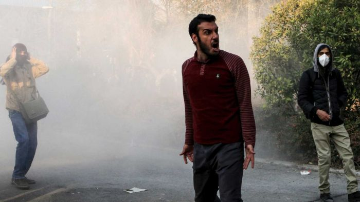 A man, standing in a cloud of smoke in the street, yells.