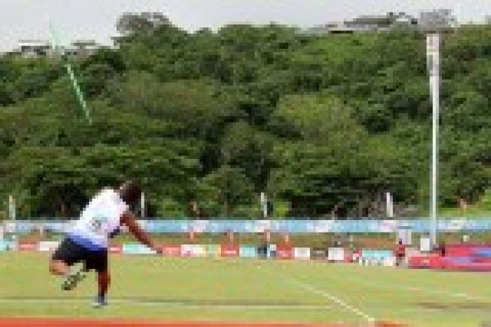 Taken from behind, this picture shows Iosefo releasing the javelin upwards with tropical jungle in the background.
