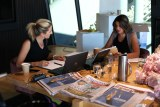 Kate Tozer and Kelli Underwood sitting in front of lap tops with newspapers on table.