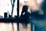 A man looks at a laptop silhouetted against a cafe window.