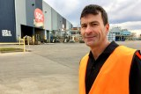 SPC Manager David Frizzell in high vis vest standing outside SPC factory in Shepparton Victoria, with SPC sign in background.