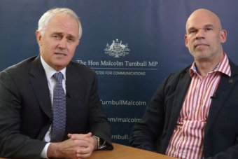 Malcolm Turnbull clasps his hands together on a desk. He sits next to Paul Shetler. Both men are wearing suits.