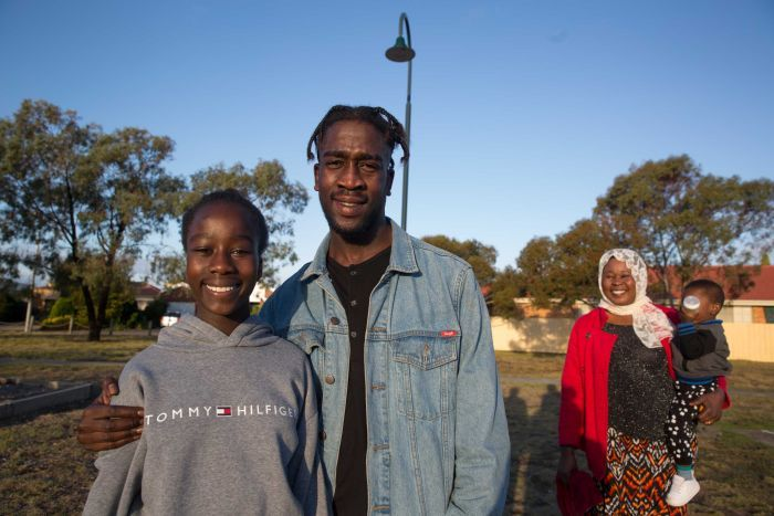 Kadiga watches on as Mohamed poses for a photo with his younger sister Monahil.