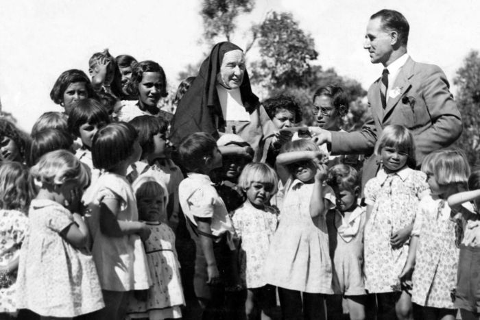 A black-and-white photo shows a nun surrounded by children, receiving a cheque from a man in a suit.