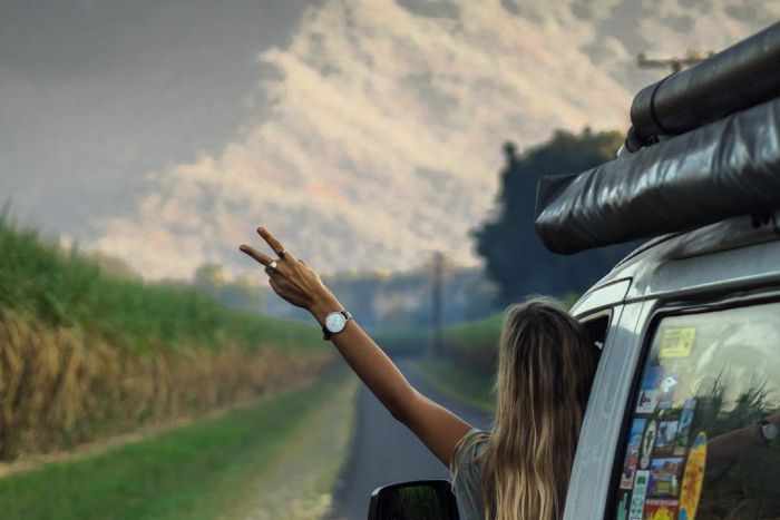 A person leans out of a van, traveling towards a mountain.