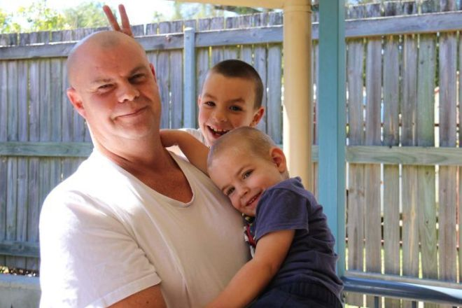 A man holding his two young sons in a backyard