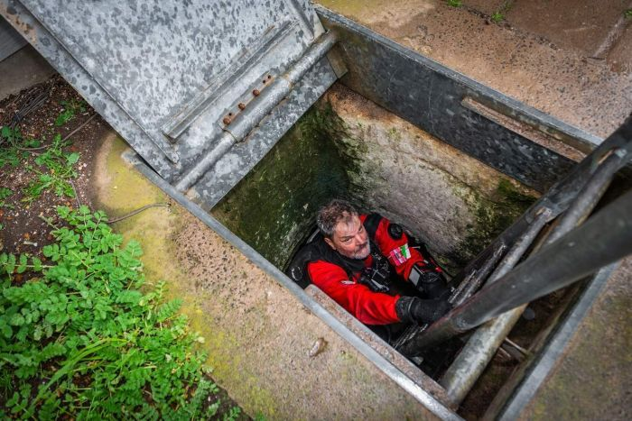 A diver lowers himself into Tank Cave.