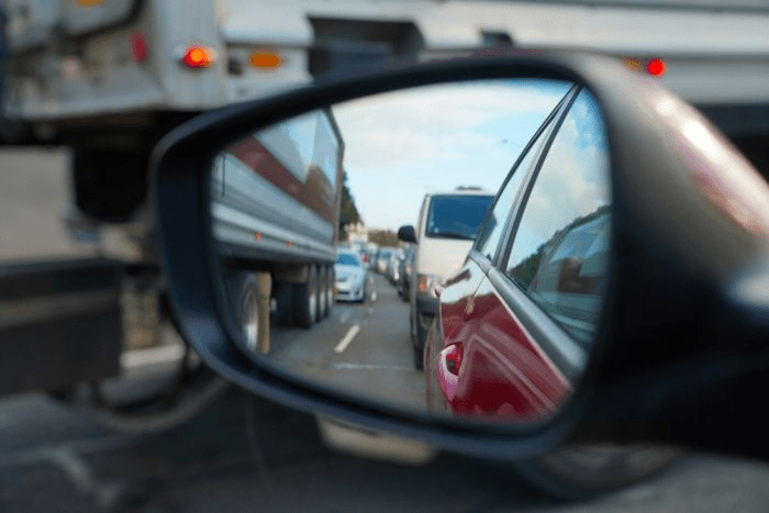 A side car mirror reflects Sydney traffic in peak hour. There are trucks, vans, and cars lined up.