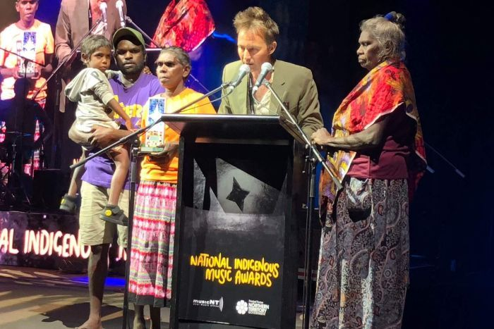 Michael Hohnen and members of G. Yunupingu's family stand around a lectern, one speaks into a microphone