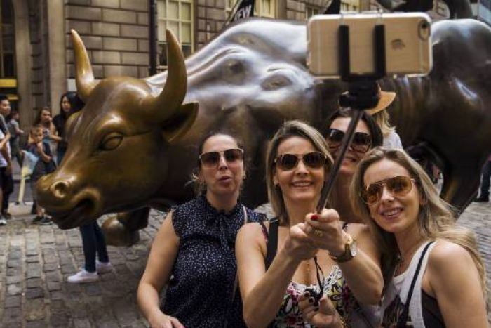 Tourists pose with Wall Street bull
