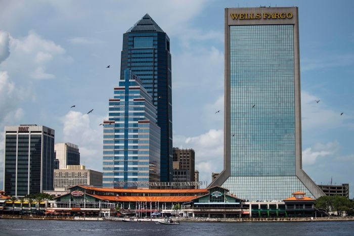 View from the water of a low-set dining and enertainment precinct, with signs saying Jacksonville Landing, with two skyscrapers